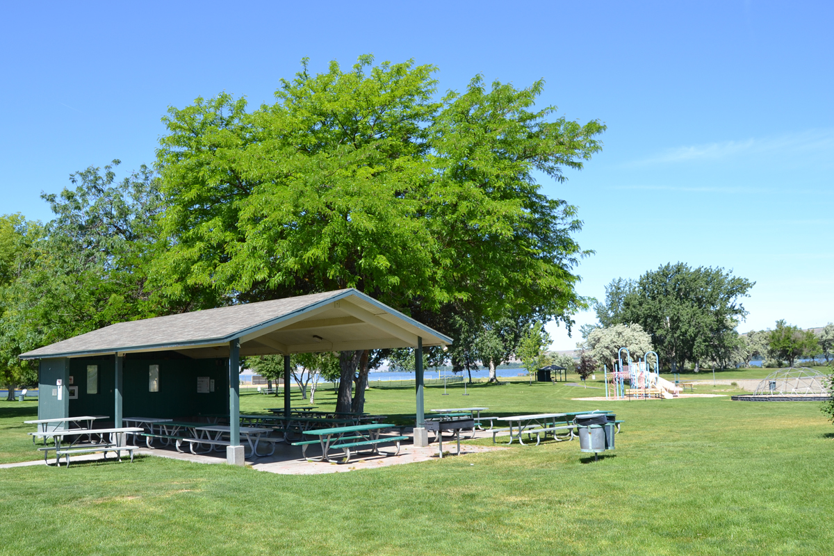 Bright green grass and blue skies shine on a covered pavilion at Boardman Park.