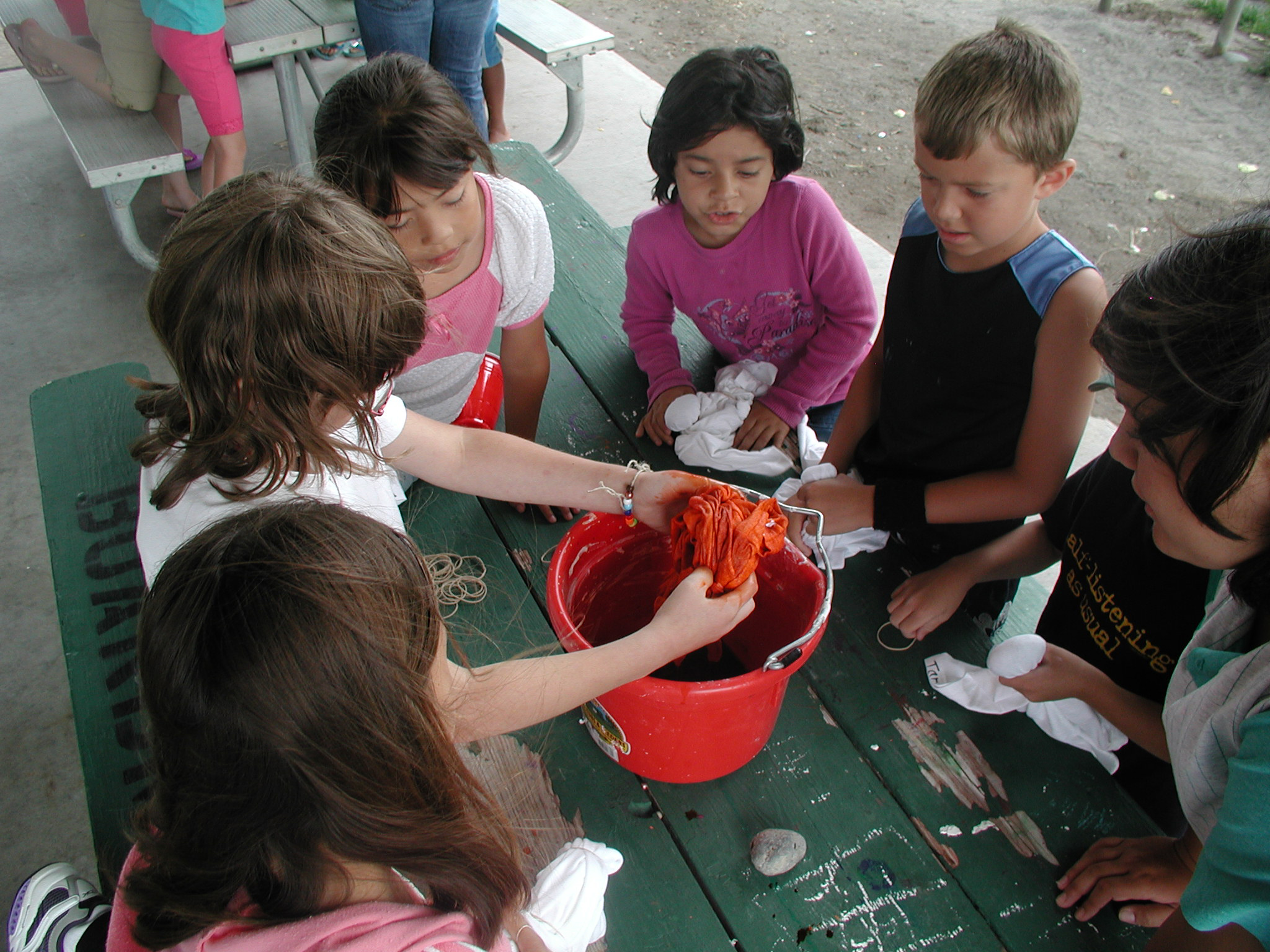 Kids participating in a fund outdoor tye dying activity.