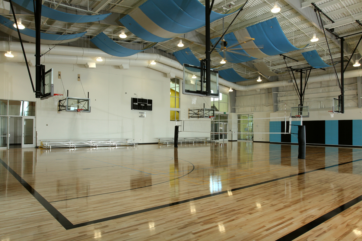 Wide open gymnasium with multiple basketball courts and volleyball net.